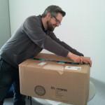 Daniel packt Paket mit hörer_innenfinanzierter Ausrüstung aus.